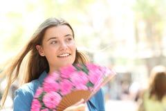Happy woman using a fan walking in the street on summer royalty free stock photo