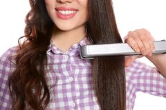 Happy woman using hair iron on white background stock photos