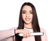Happy woman using hair iron on white stock photo