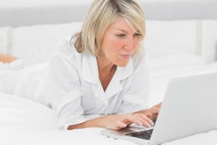 Happy woman using her laptop on her bed Royalty Free Stock Photo