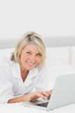 Happy woman using her laptop on her bed looking at camera Stock Photo