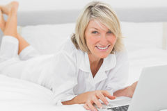 Happy woman using her laptop on her bed smiling at camera Stock Image