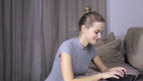 Happy woman using her laptop at home. Woman typing on a computer. Happy woman using her laptop at home. Woman typing on a modern laptop stock footage
