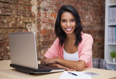 Happy woman using her laptop smiling at camera Stock Photos