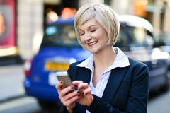 Happy woman using her mobile phone Royalty Free Stock Photography