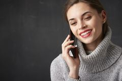 Happy woman using her mobile phone and talking with somebody. Studio portrait of attractive young woman sitting with her mobile phone and talking with somebody Stock Photos