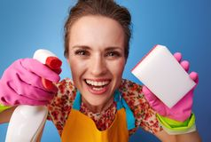 Happy woman using kitchen sponge and cleaning detergent on blue. Big cleaning time. happy modern woman with rubber gloves using kitchen sponge and cleaning stock photo