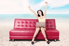 Happy woman using laptop at the beach Stock Photos