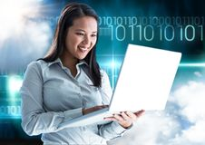 Happy woman using laptop with binary codes in background Royalty Free Stock Image