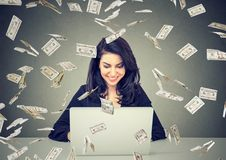 Happy woman using a laptop building online business under dollar bills falling down. royalty free stock photography