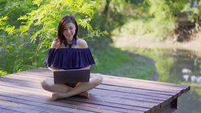 Happy woman using laptop computer on wooden jetty. Happy woman using laptop computer on a wooden jetty stock video