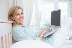 Happy woman using laptop in her bed Stock Images