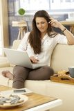 Happy woman using laptop at home on sofa Royalty Free Stock Image