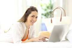 Woman using a laptop looking at you on vacations Royalty Free Stock Image