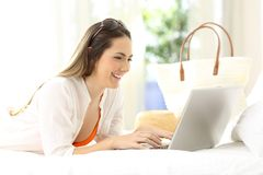 Woman using a laptop on a bed on summer vacations Royalty Free Stock Image
