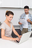 Happy woman using laptop while partner reads the newspaper Royalty Free Stock Photo