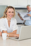 Happy woman using laptop with partner standing with the paper Stock Image