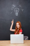 Happy woman using laptop and pointin up over blackboard background Stock Photo