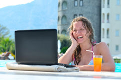 Happy woman is using laptop in pool Stock Images