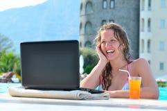Happy woman is using laptop in pool. Beautiful woman is using laptop in the swimming pool Stock Images