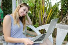 Happy woman using laptop and sitting in exotic garedn with palms in background. stock photo