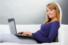 Happy woman using laptop sitting on sofa, modern technology Royalty Free Stock Photography