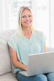 Happy woman using laptop while sitting on sofa Royalty Free Stock Image