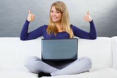 Happy woman using laptop sitting on sofa and showing thumbs up Royalty Free Stock Photo