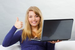 Happy woman using laptop sitting on sofa and showing thumbs up Stock Images