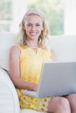 Happy woman using laptop on sofa Stock Image