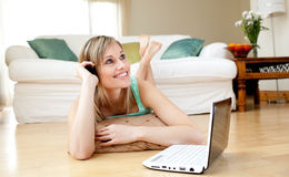Happy woman using a laptp lying on the floor Royalty Free Stock Image