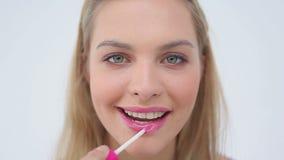 Happy woman using a lip brush Stock Photography