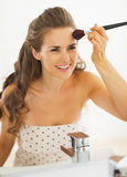 Happy woman using makeup brush in bathroom Royalty Free Stock Photo