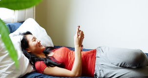 Happy woman using mobile phone in bedroom. At home stock video
