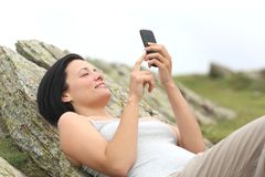 Happy woman using a mobile phone lying in the mountain Stock Photo