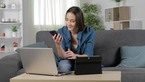 Woman using multiple devices and talking on phone. Happy woman using multiple devices and talking on phone at home stock footage