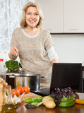 Happy woman using notebook while cooking soup Royalty Free Stock Image