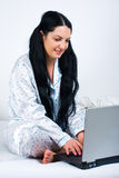 Happy Woman Using Notebook On Bed Stock Images