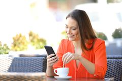 Happy woman using phone stirring coffee in a bar. Happy woman using smart phone stirring coffee in a bar terrace royalty free stock photography