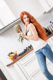 Happy Woman Using a Pineapple as Microphone Stock Photo