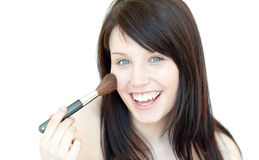 Happy woman using a powder brush Stock Images