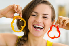 Happy woman using slice of bell pepper as earrings Royalty Free Stock Images