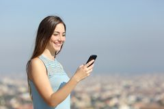 Happy woman using a smart phone in a city outskirts. Happy woman using a smart phone walking in a city outskirts a sunny day royalty free stock photography