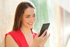 Happy woman using smart phone in a colorful street stock photography