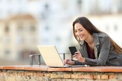 Happy woman using phone and laptop in a balcony royalty free stock images