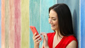 Woman using phone in a colorful wall. Happy woman using smart phone leaning in a colorful wall in the street stock video