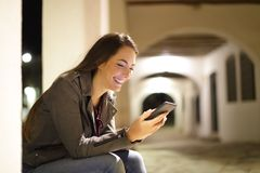 Happy woman using a smart phone sitting in the night. Happy woman using a smart phone sitting in the street in the night royalty free stock photography