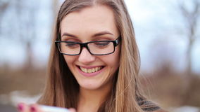 Happy woman using a smart phone in the street with an unfocused background stock video footage