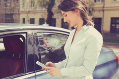 Happy woman using smart phone to check status, control her new car Royalty Free Stock Images