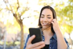 Happy woman using smart phone touching hair in a park stock photography